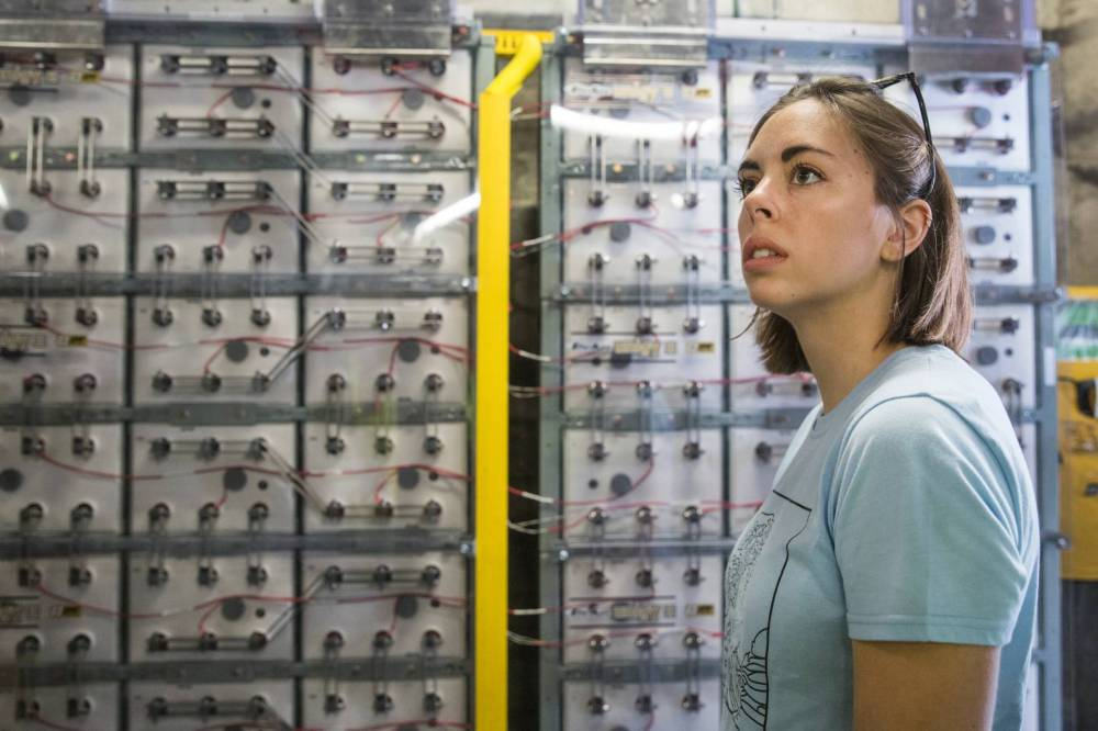Erin Redding standing in front of battery bank