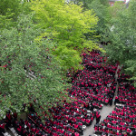 A birds eye view of a sea of Business School Graduates in red robes during Commencement morning exercises