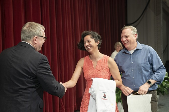 Student shakes Dean Warnick's hand
