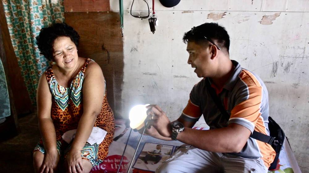 Villagers indoors shining a light
