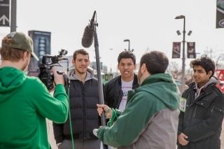 Three students being interviewed outside at MetLife Stadium.