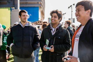 Three students playing video games at MetLife Stadium.