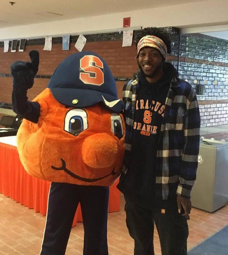 student standing next to Otto the Orange mascot
