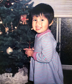 Gemma as a toddler standing next to a Christmas tree