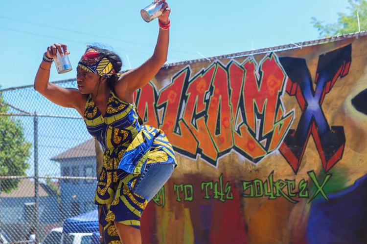 Latanya dances wearing African clothing with Malcom X in a mural behind her