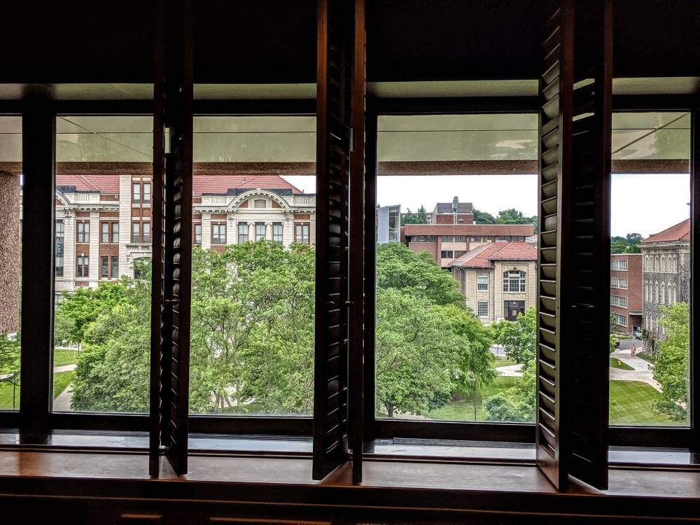 campus view of buildings through interior windows