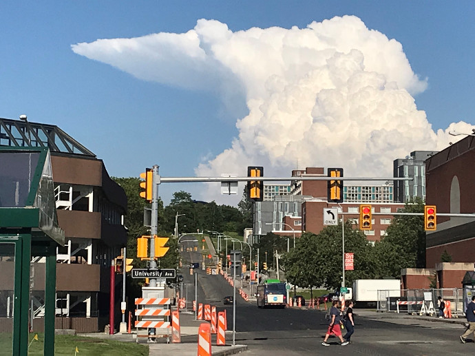 large cloud formation over city street and buildings