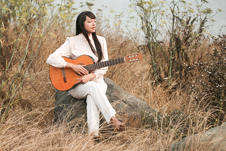 Diana Gameros in a field sitting on a rock with a guitar in her hand with her eyes closed