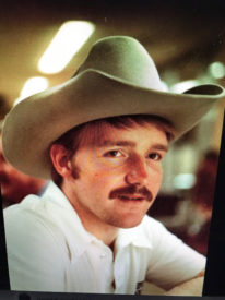 Portrait of Mike Combs wearing a cowboy hat in 1985
