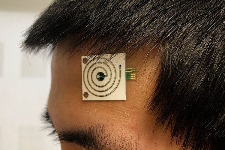 A close up shot of a new sweat sensor on a person's forehead