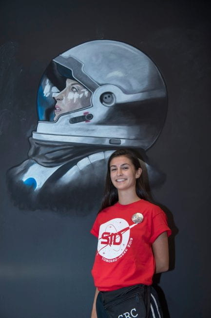 """Fernanda """"Fern"""" Horrillo poses in front of her chalk drawing for Sid Richardson College's O-Week theme. (Photo by Tommy LaVergne)"""