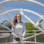 Center for Astrophysics astronomer Laura Kreidberg framed by a metal structure