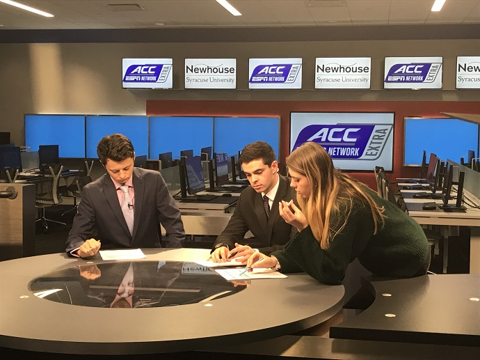 woman speaking with two men at anchor desk