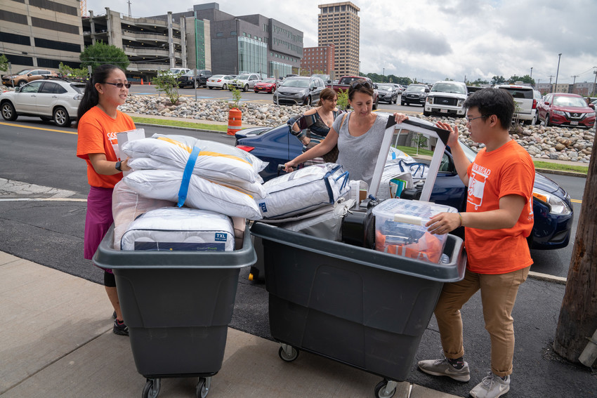students loading bins with items from new students