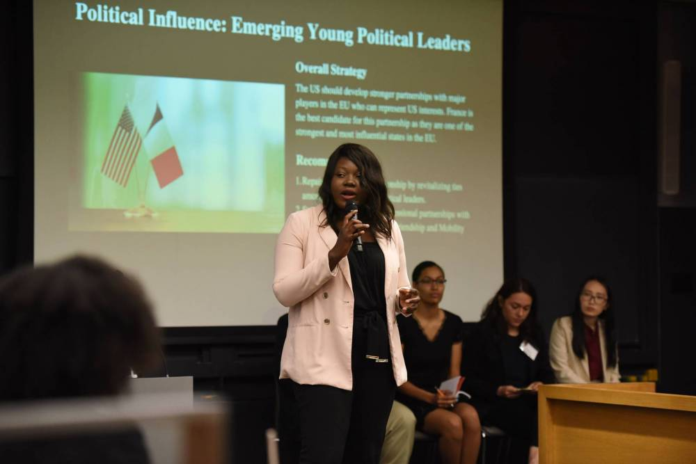 """A woman speaks to an auditorium-style classroom full of undergraduates in front of a projection that reads: """"Political Influence: Emerging Young Political Leaders"""""""
