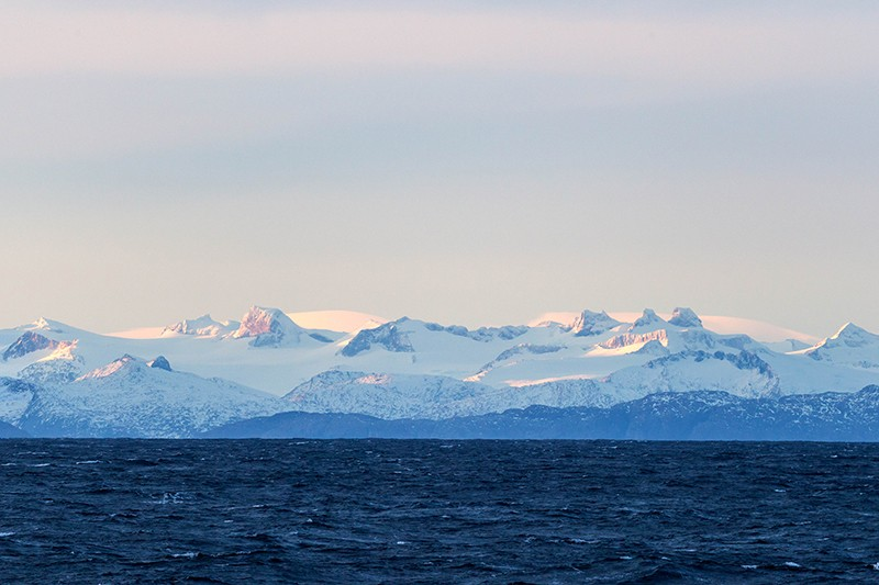 The white and blue landscape of the snowy Patagonian mountains by the ocean.