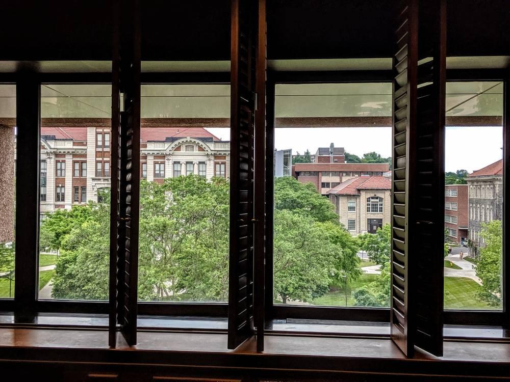 campus view of buildings through interior windows