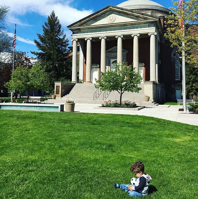 small child sitting on lawn in front of Hendricks Chapel