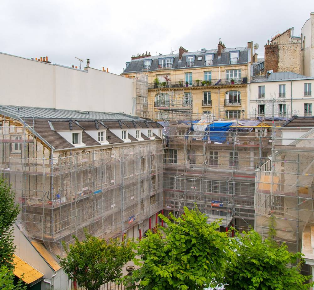 Photograph of the Reid Hall courtyard with the buildings covered by scaffolding