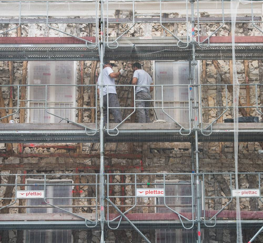 Photograph of workers on scaffolding re-facing a building