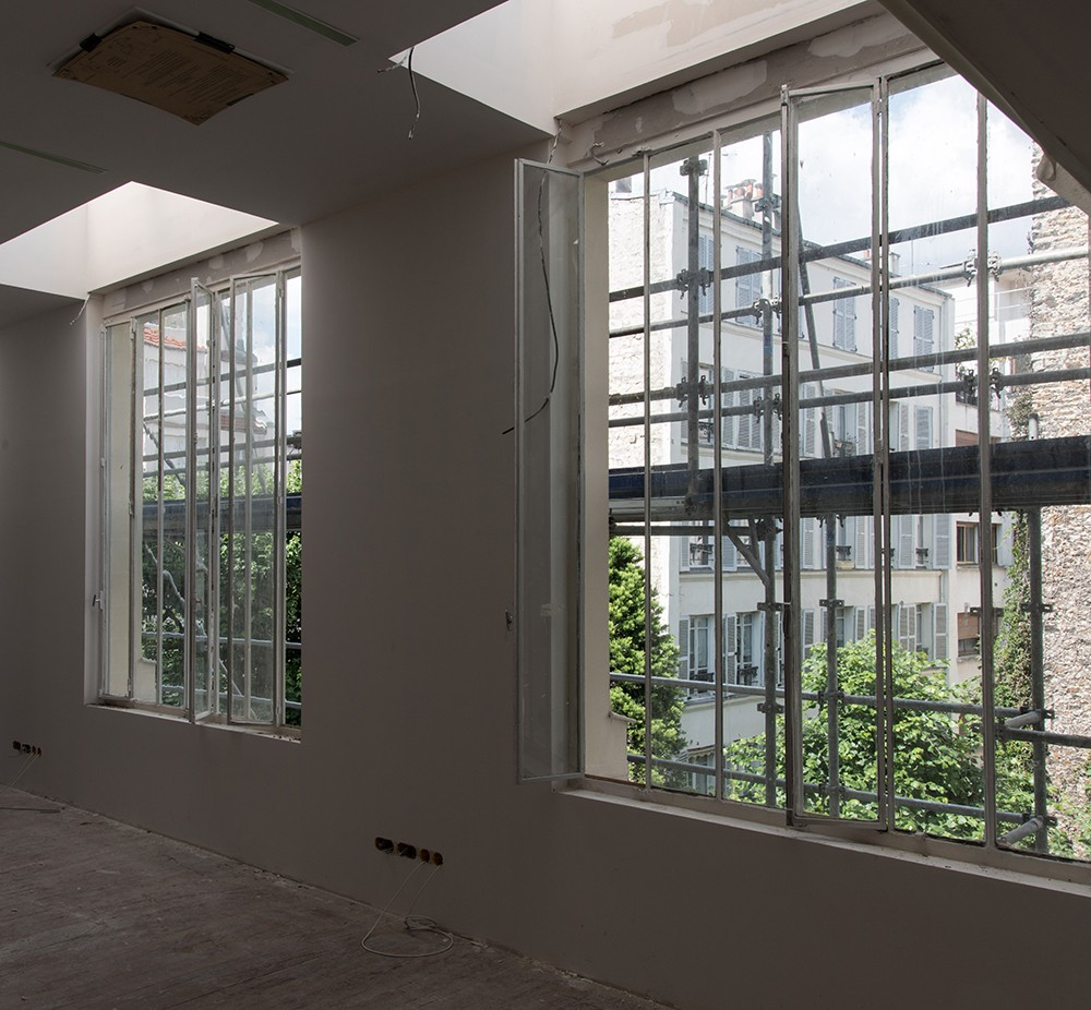 Photo of two windows from inside a building, showing scaffolding and construction