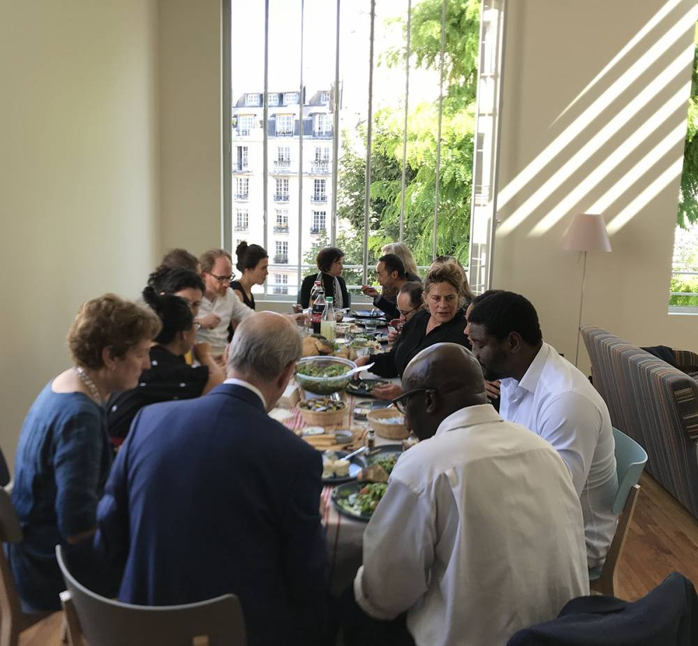 Photo graph of a group of people sitting down to lunch inside a big room, in front of a big window with light streaming in