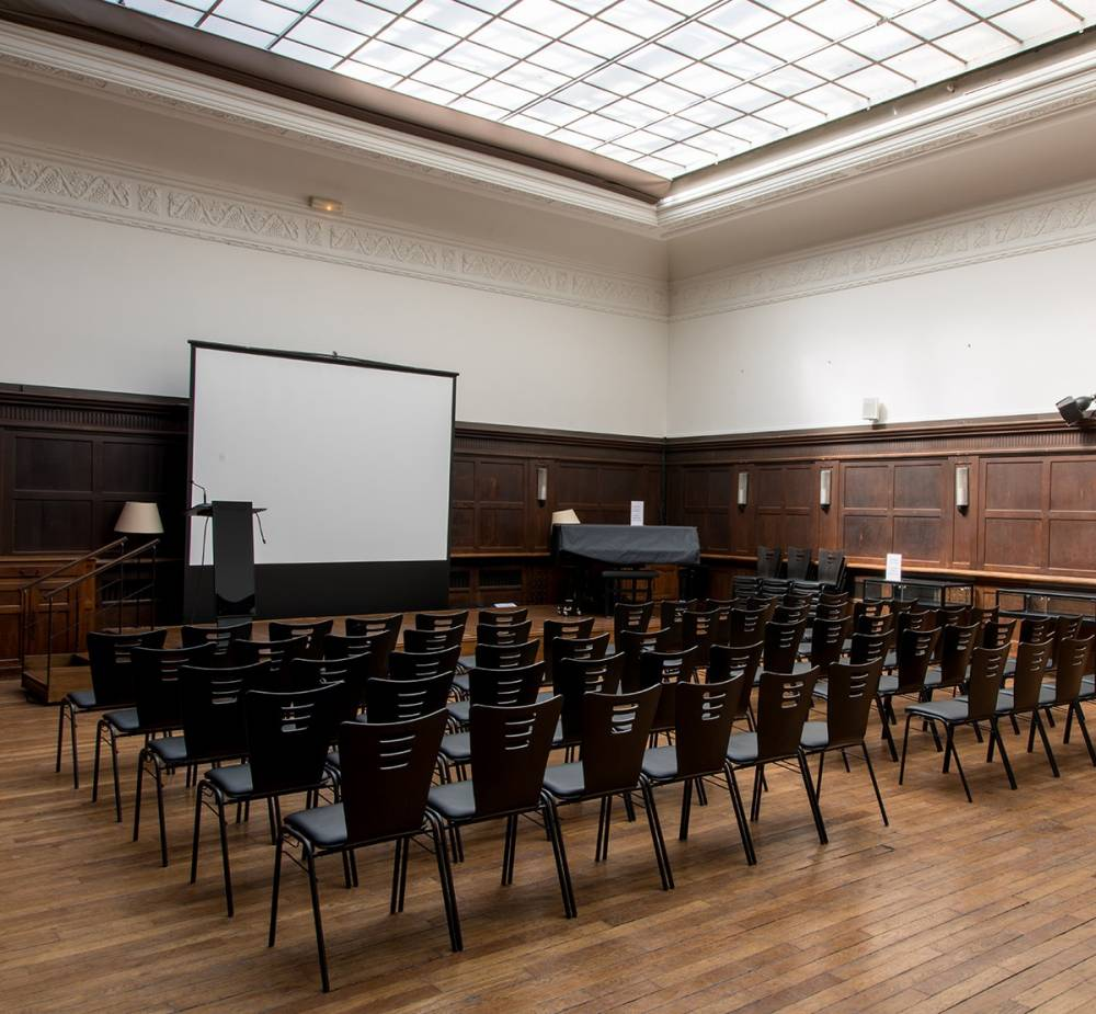 Photograph of a large room with chairs lined up in front of a screen and podium; skylight overhead