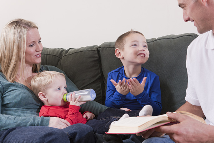 Boy signing the word 'Book' in American Sign Language while studying with his parents