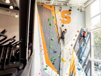 people climbing on indoor rock wall