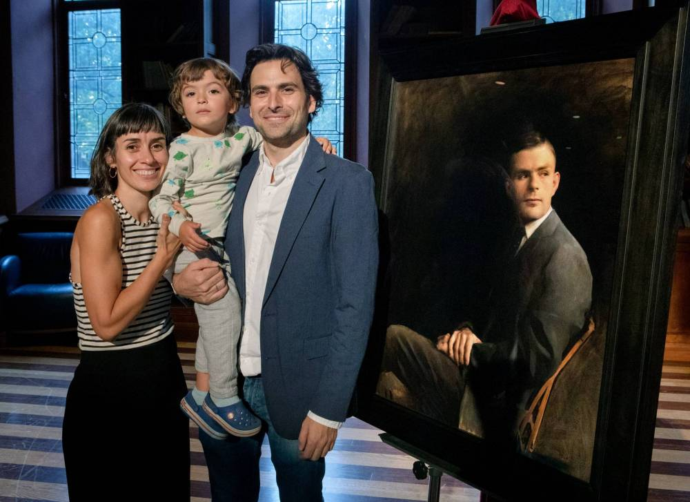 The artist and his family pose next to the portrait of Alan Turing