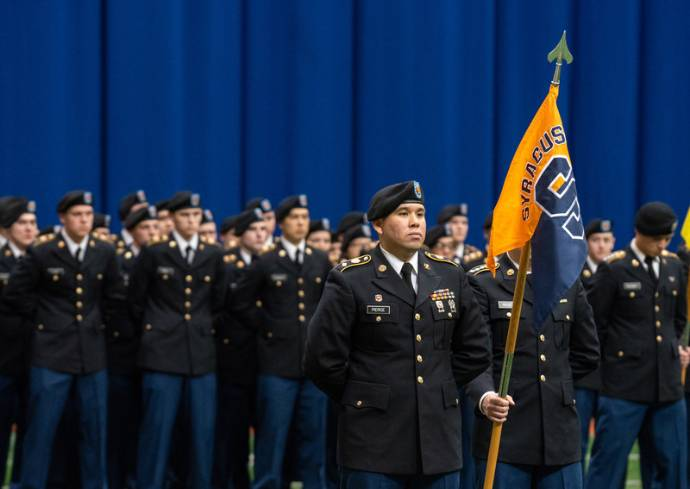 military service members stand with flag