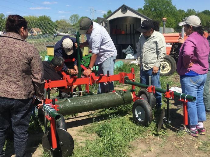 people fixing farm equipment