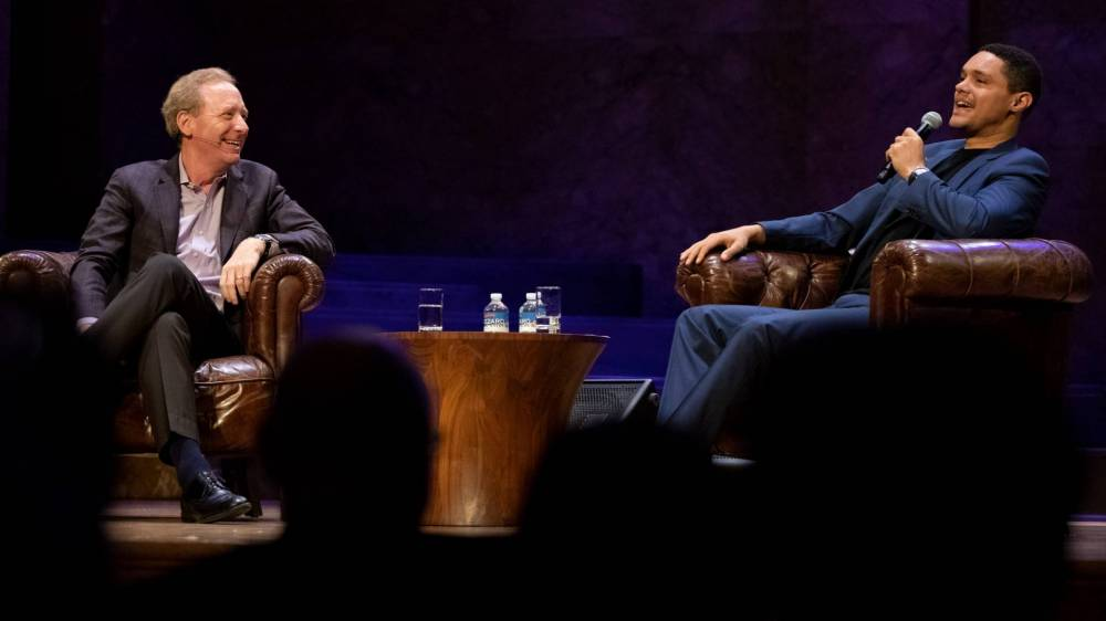 Two men sit in armchairs on a stage