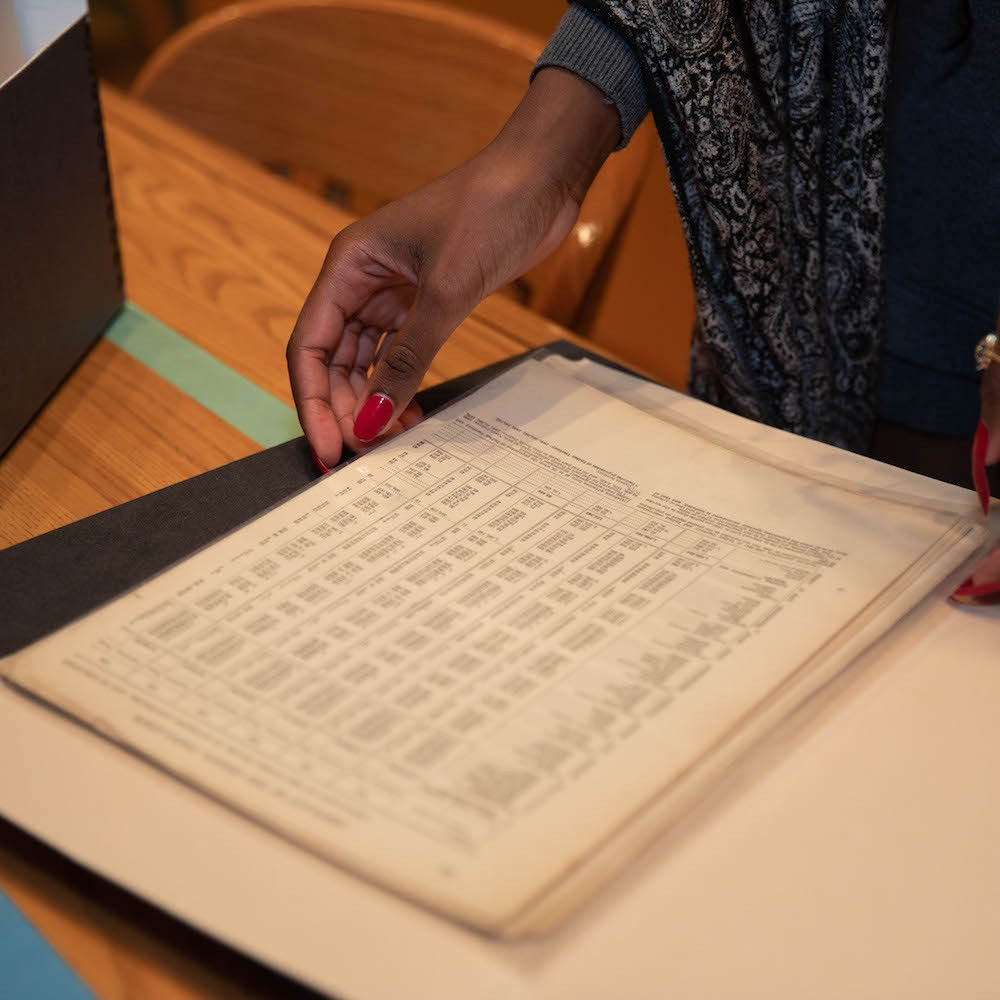 A women with red nails holding an old ledger