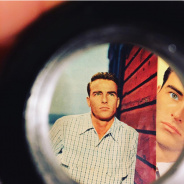 """Still image from """"Making Montgomery Clift"""" film, showing a circular viewfinder with images of the actor standing against a red-planked wall"""