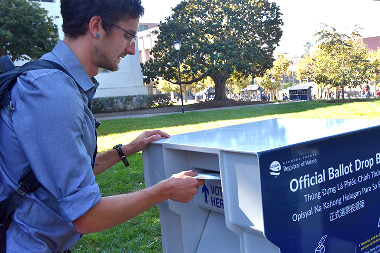 male students casts his ballot on campus