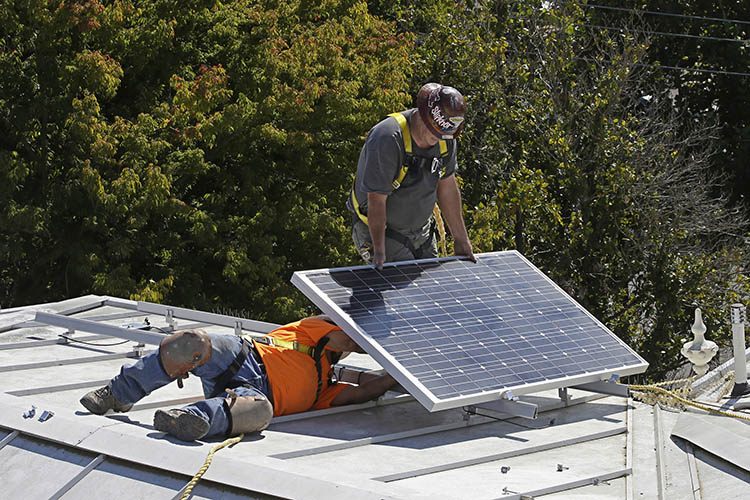 two men install solar panels on the roof of a home in California