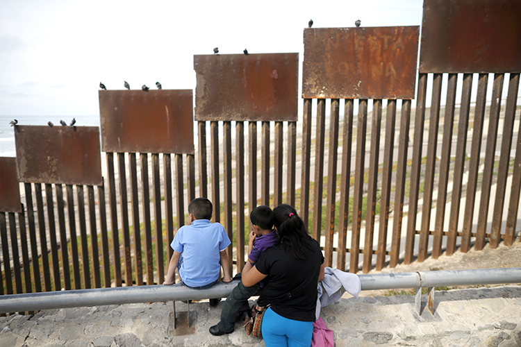 a family looks towards metal bars marking the United States border where it meets the Pacific Ocean