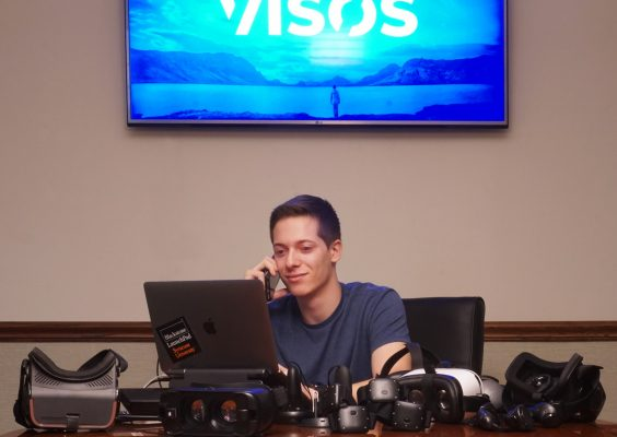 Young man sitting at computer with VISOS sign above him.