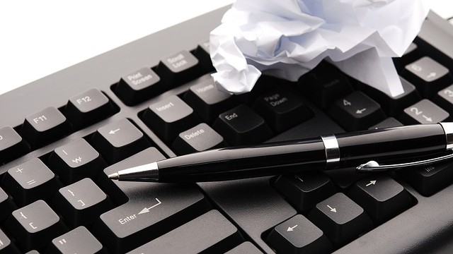 Keyboard with crumpled paper and pen