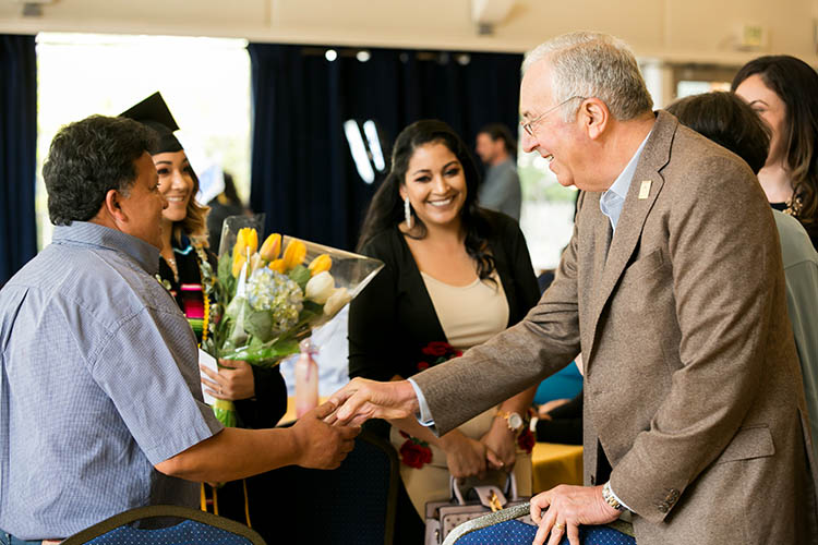 Robert Haas shakes the hand of a man while a woman in a cap and gown looks on