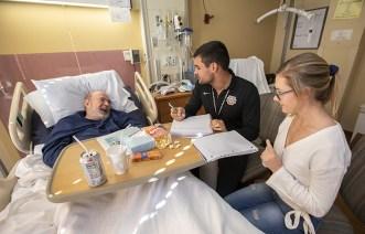 "Undergraduates Alex Gazo and Helen Stephens interview veteran James Claspill for ""My Life, My Story."" (Photo: Joe Angeles/Washington University)"