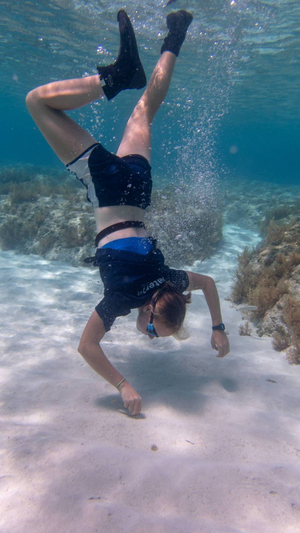 A student dives in tropical waters to get scientific samples of sand