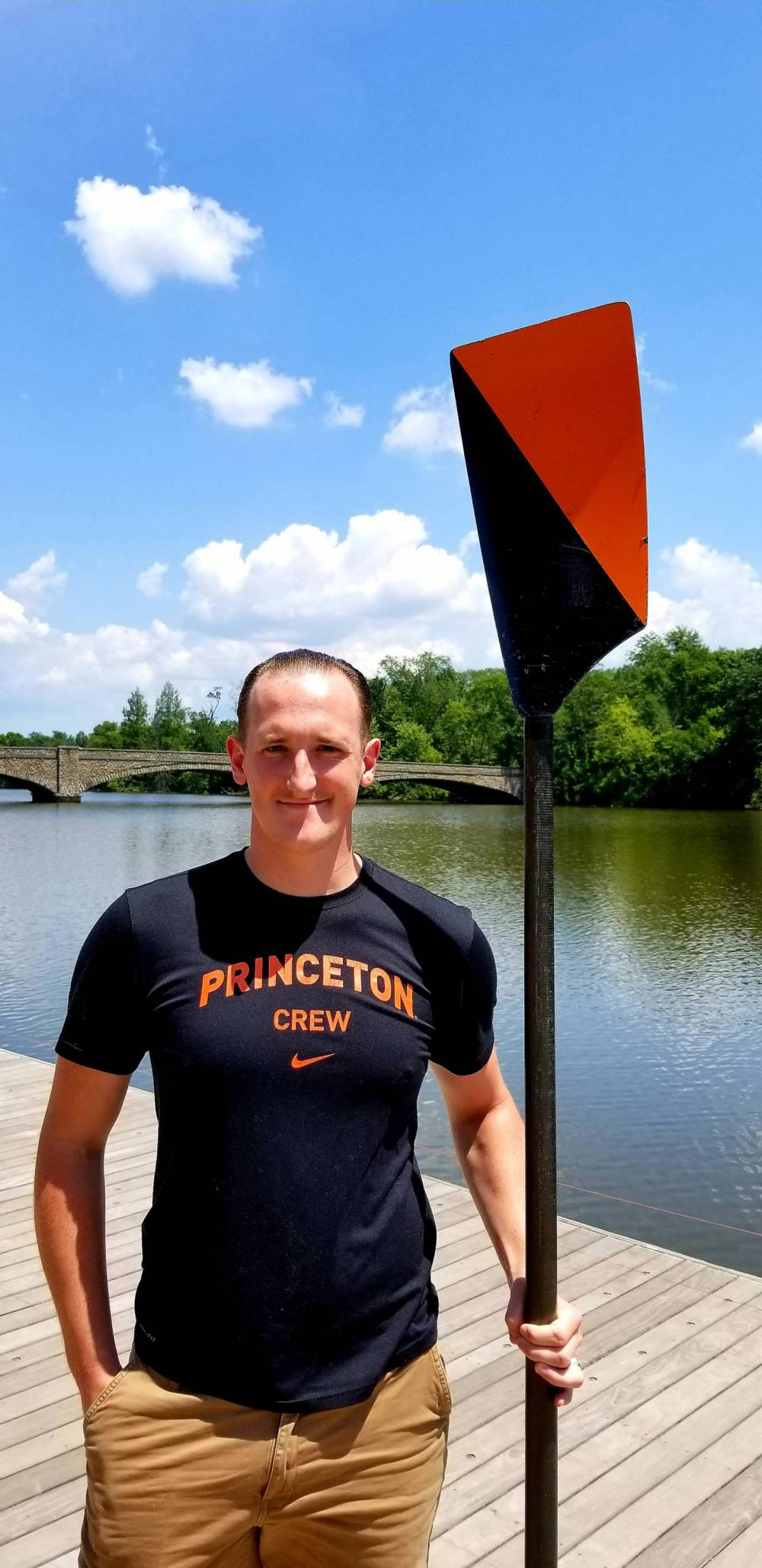 Student holding black and orange rowing oar