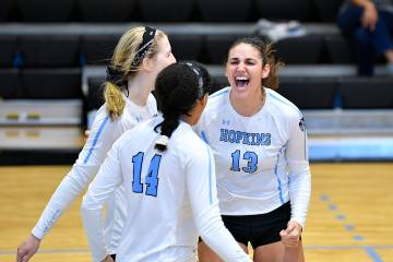 Johns Hopkins volleyball players celebrate