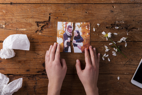Hands ripping photo of couple in half