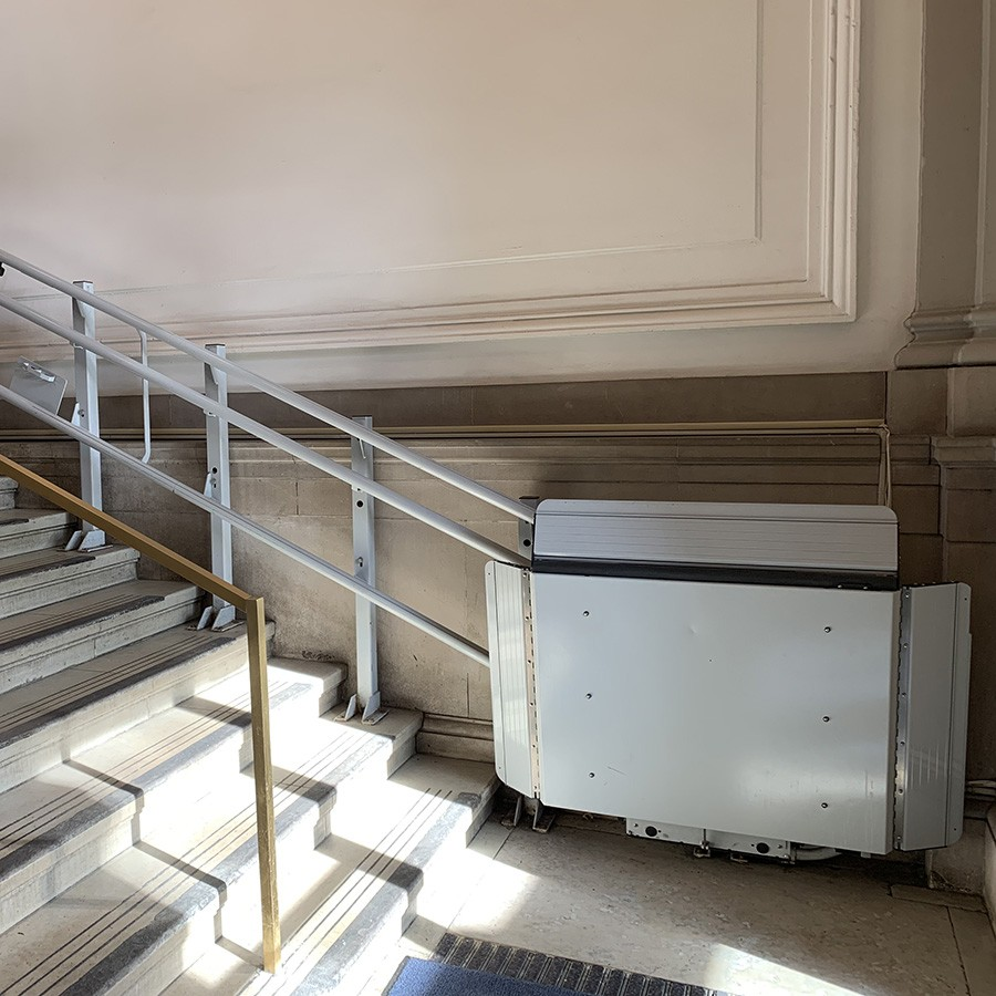 A wheelchair lift sits at the bottom of a staircase in Lewisohn Hall.