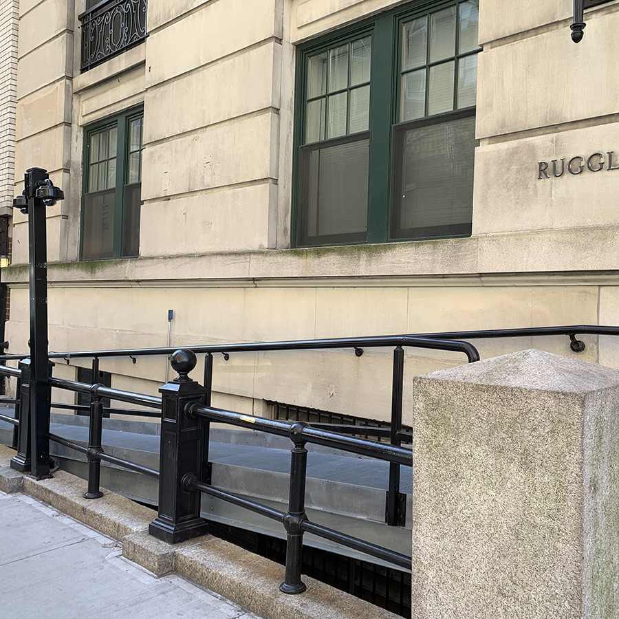 A metal ramp leads up to the entrance of the Ruggles building.