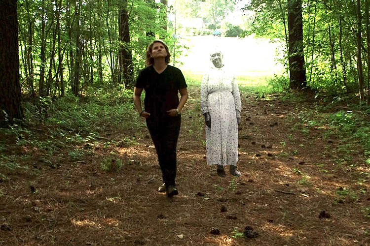 Frances Causey walks in the woods next to a representation of a slave