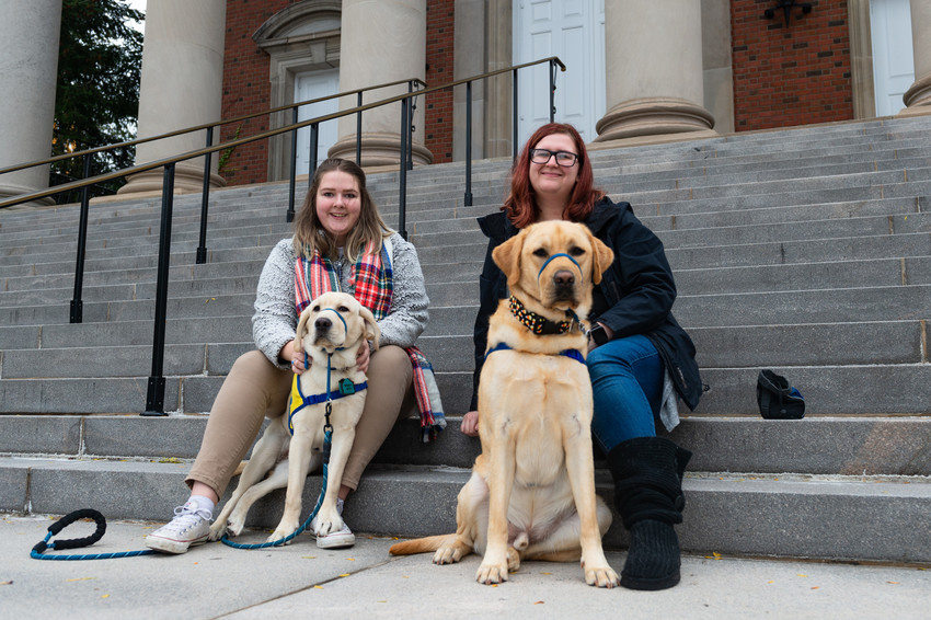 two women sitting with two dogs on steps of Hendricks Chapel